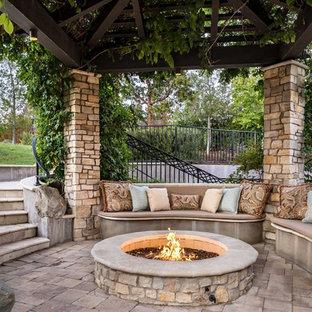 Foto di un patio o portico classico di medie dimensioni e dietro casa con un gazebo o capanno, un focolare e pavimentazioni in pietra naturale
