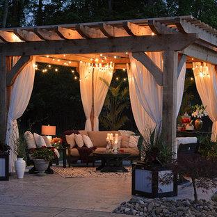 Imagen de patio clásico renovado, en patio trasero, con losas de hormigón y pérgola