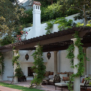 Photo of a mediterranean patio in Los Angeles with a fire feature and a pergola.