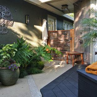 Idee per un piccolo patio o portico tropicale dietro casa con pedane e un tetto a sbalzo