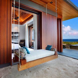 Esempio di un grande patio o portico tropicale con un tetto a sbalzo