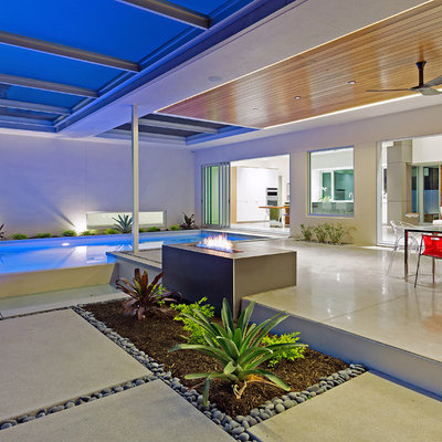 Inspiration for a large contemporary backyard concrete patio remodel in Tampa with a fire pit and a roof extension