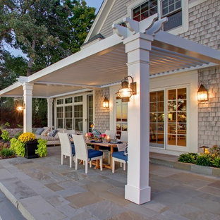 This is an example of a large traditional backyard patio in New York with a pergola.
