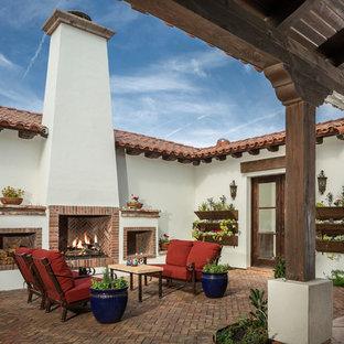 Immagine di un patio o portico mediterraneo in cortile con pavimentazioni in mattoni, nessuna copertura e un caminetto