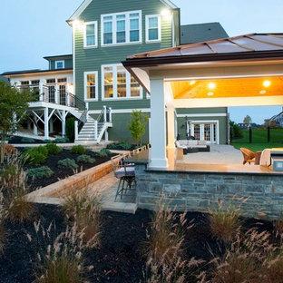 Immagine di un grande patio o portico tradizionale dietro casa con pavimentazioni in mattoni e un gazebo o capanno