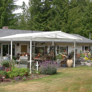 Design ideas for a medium sized farmhouse back patio in Seattle with an outdoor kitchen, concrete slabs and an awning.