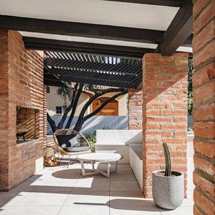 Foto di un patio o portico stile americano con un caminetto e una pergola