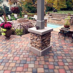 Immagine di un patio o portico eclettico di medie dimensioni e dietro casa con fontane, pavimentazioni in cemento e una pergola