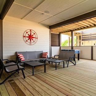 Esempio di un ampio patio o portico stile marinaro dietro casa con pedane e un tetto a sbalzo