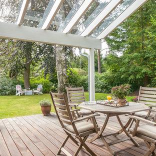 Esempio di un patio o portico nordico dietro casa con pedane e un tetto a sbalzo