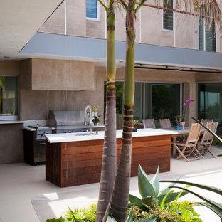 Immagine di un grande patio o portico tropicale dietro casa con lastre di cemento e un tetto a sbalzo