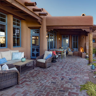 Example of a southwest brick patio design in Albuquerque with a roof extension
