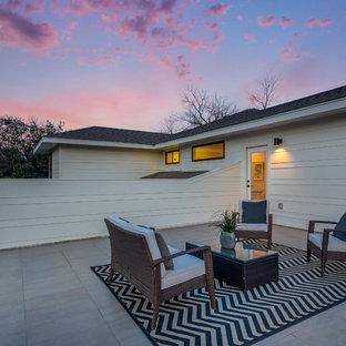 Immagine di un patio o portico minimalista di medie dimensioni e nel cortile laterale con piastrelle