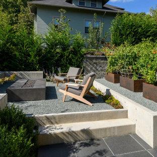 Ispirazione per un patio o portico moderno di medie dimensioni e dietro casa con un focolare, graniglia di granito e un tetto a sbalzo