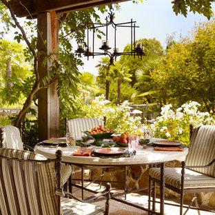 Cette image montre une terrasse avec une cuisine extérieure méditerranéenne avec des pavés en pierre naturelle et une pergola.