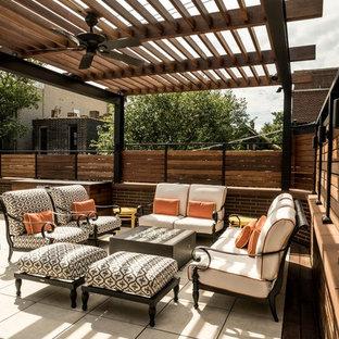 Foto di un patio o portico minimal di medie dimensioni e dietro casa con un focolare, piastrelle e una pergola
