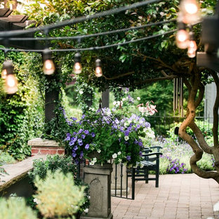 Inspiration for a mid-sized timeless courtyard brick patio container garden remodel in Seattle with a pergola