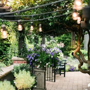 Cette photo montre une terrasse avec des plantes en pots arrière chic de taille moyenne avec des pavés en brique et une pergola.