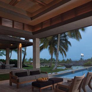 Ispirazione per un ampio patio o portico etnico dietro casa con piastrelle e un tetto a sbalzo