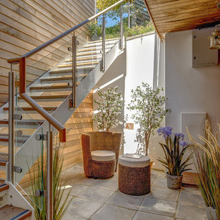 This is an example of a contemporary courtyard patio in Devon with a roof extension.