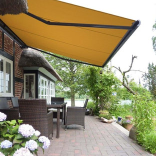 Design ideas for a mid-sized contemporary backyard patio in Other with brick pavers and an awning.