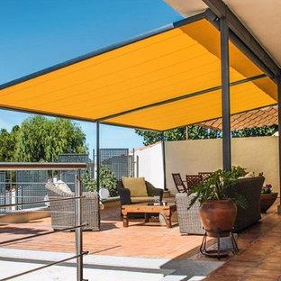 Ispirazione per un patio o portico design di medie dimensioni e dietro casa con piastrelle e un parasole