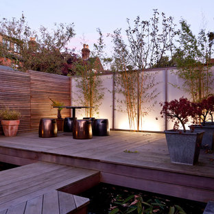 This is an example of a contemporary patio in London with no cover and a water feature.