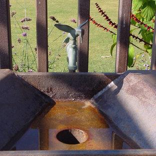Idee per un grande patio o portico mediterraneo dietro casa con una pergola e lastre di cemento