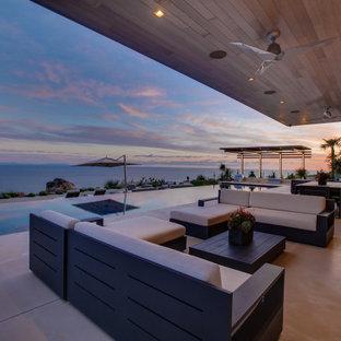 Esempio di un ampio patio o portico moderno dietro casa con un focolare e una pergola
