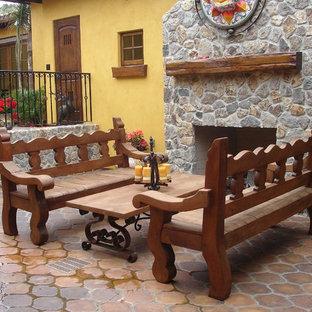 Immagine di un patio o portico boho chic in cortile con un focolare, piastrelle e nessuna copertura