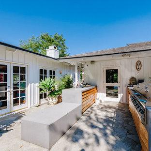Immagine di un ampio patio o portico boho chic dietro casa con pavimentazioni in pietra naturale e nessuna copertura