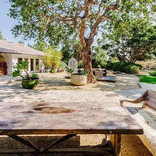 Foto di un ampio patio o portico boho chic dietro casa con pavimentazioni in pietra naturale e nessuna copertura