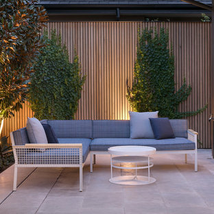 This is an example of a small contemporary backyard patio in Melbourne with natural stone pavers.