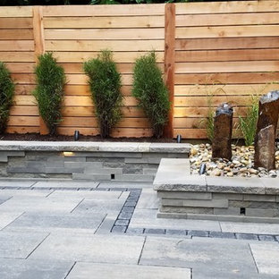 Example of a mid-sized minimalist backyard tile patio design in Philadelphia with no cover