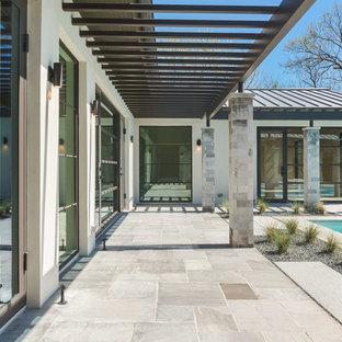 Aménagement d'une grande terrasse arrière classique avec un gravier de granite et une pergola.