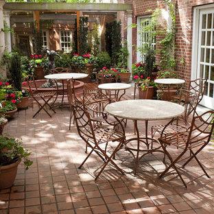 Imagen de patio tradicional, en patio, con jardín de macetas y suelo de baldosas