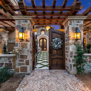 Foto di un ampio patio o portico shabby-chic style davanti casa con un focolare, pavimentazioni in mattoni e un gazebo o capanno