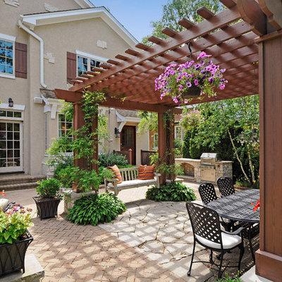 Large elegant backyard stone patio photo in Chicago with a pergola