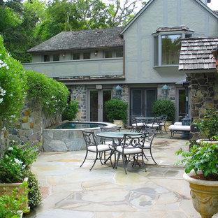 Esempio di un ampio patio o portico stile americano dietro casa con pavimentazioni in pietra naturale