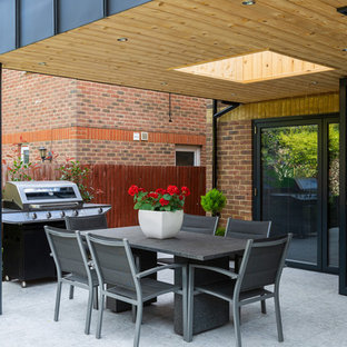 Design ideas for a contemporary back patio in Hertfordshire with an outdoor kitchen, concrete slabs and a roof extension.