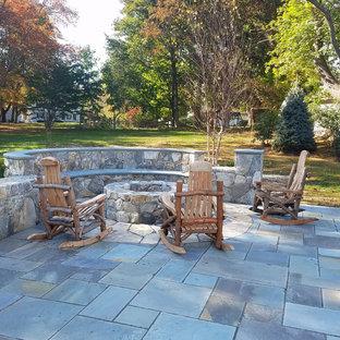 Großer Klassischer Patio hinter dem Haus mit Feuerstelle und Natursteinplatten in New York