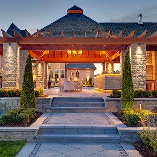 Esempio di un patio o portico classico dietro casa con cemento stampato e una pergola