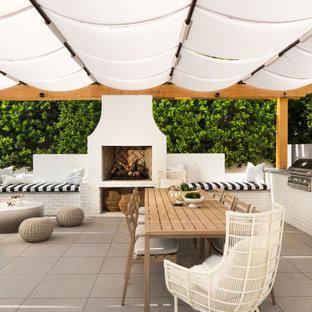 Immagine di un grande patio o portico design dietro casa con pavimentazioni in cemento e un parasole