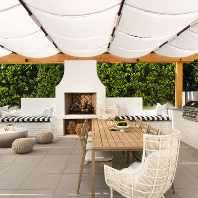 Example of a large trendy backyard concrete paver patio kitchen design in Phoenix with an awning