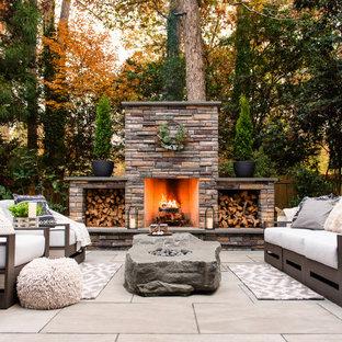Immagine di un patio o portico moderno di medie dimensioni e dietro casa con un caminetto e pavimentazioni in pietra naturale