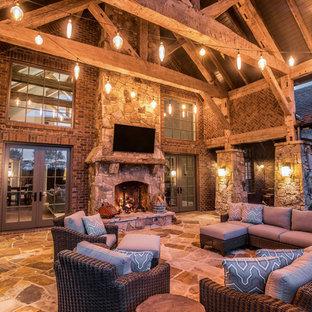 Ispirazione per un grande patio o portico stile rurale dietro casa con un caminetto, piastrelle e un tetto a sbalzo