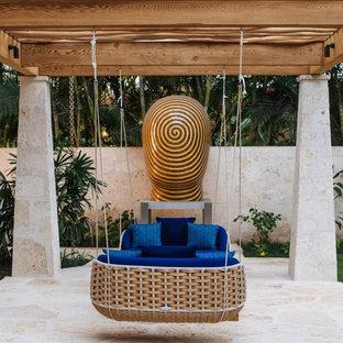 Foto de patio tropical, de tamaño medio, en patio trasero, con pérgola y adoquines de piedra natural