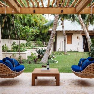 Ispirazione per un patio o portico tropicale di medie dimensioni e dietro casa con pavimentazioni in pietra naturale, una pergola e un giardino in vaso
