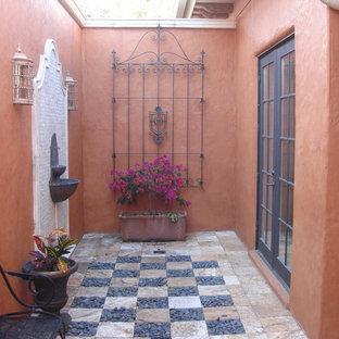Стильный дизайн: маленький дворик на внутреннем дворе в средиземноморском стиле с фонтаном и покрытием из плитки без защиты от солнца - последний тренд