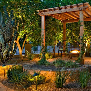 Inspiration for a mediterranean courtyard patio remodel in Phoenix with a fire pit and a pergola
